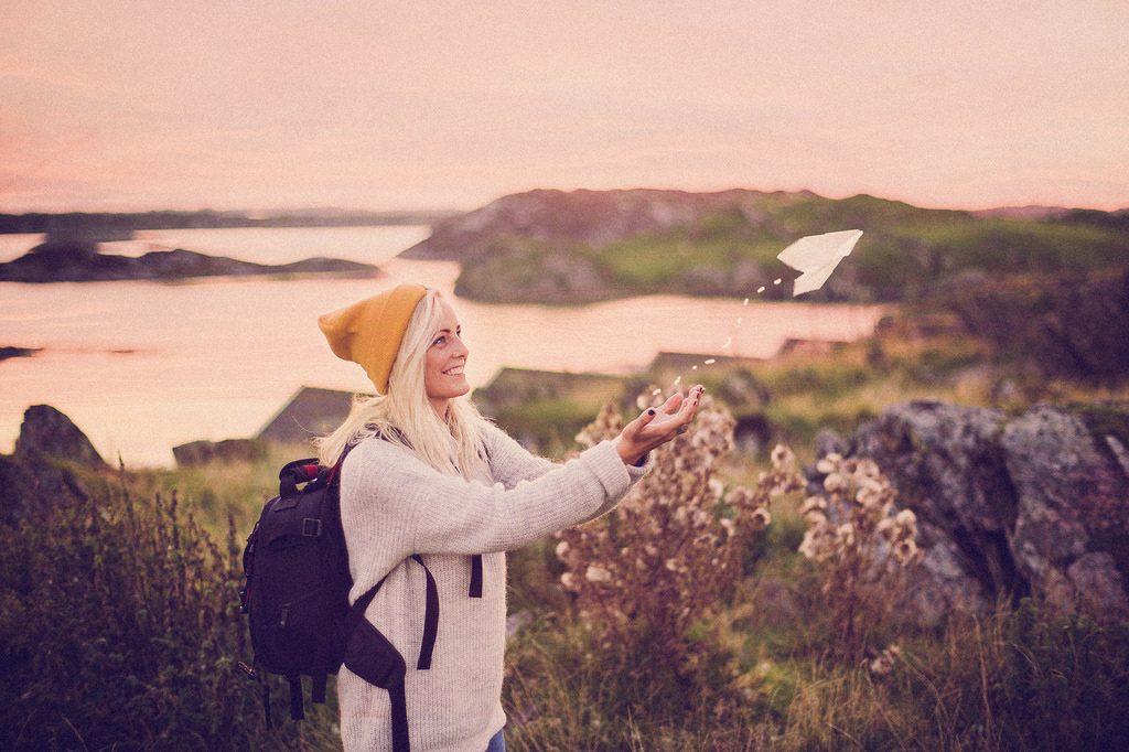 Una persona lanza un avión de papel en mitad de la naturaleza.